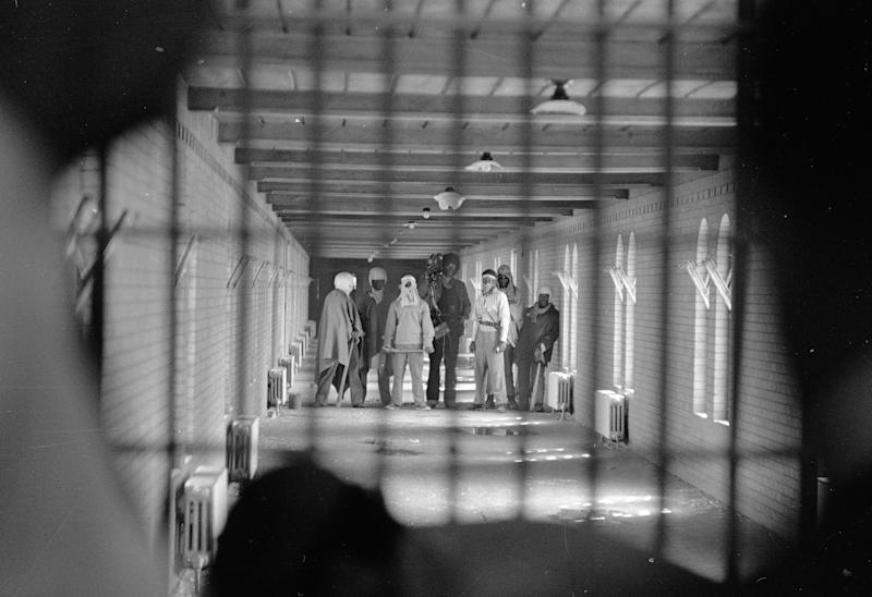FILE - In this Sept. 10, 1971 file photo, inmates wearing cloaks and football helmets stand behind bars in a corridor leading to D block as they begin negotiatiations with New York State officials after a prison uprising at Attica State Prison, in Attica, N.Y. New York's Attorney General Eric Schneiderman has asked a state judge to unseal documents about the 1971 riot and retaking of Attica state prison in the nation's bloodiest prison rebellion. (AP Photo/Bob Schutz, File)