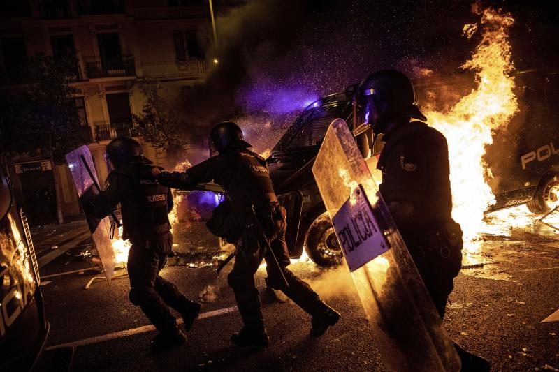 Policemen run as a police van drives over a burning barricade during clashes between protestors and police in Barcelona, Spain, Wednesday, Oct. 16, 2019. (Photo: Bernat Armangue/AP)