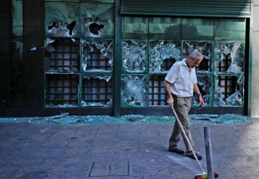 A man cleans up outside a bank that was vandalised by protesters in Lebanon's northern city of Tripoli