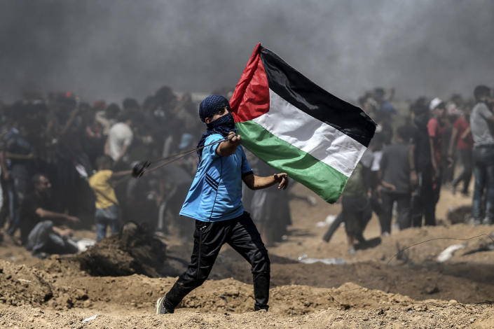 A Palestinian protestor waves his national flag during a demonstration along the border with Israel east of Jabalia in the central Gaza Strip on June 8, 2018. (Photo: Mohammed Abed/AFP/Getty Images)