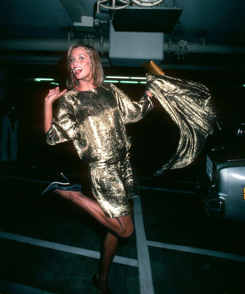 <p>Lauren Hutton's gold dress with a short hemline and attached train with large shoulder pads encapsulated the glamour — and sartorial oddities — of the decade. <em>(Photo: Getty Images)</em> </p>