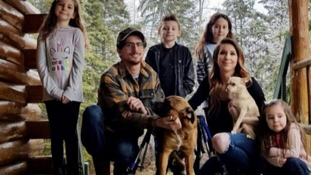 Meagan MacDonald, Jacob Murphy and their family surround Ritz on their Cardigan property this week.  (Danny Arsenault/CBC - image credit)