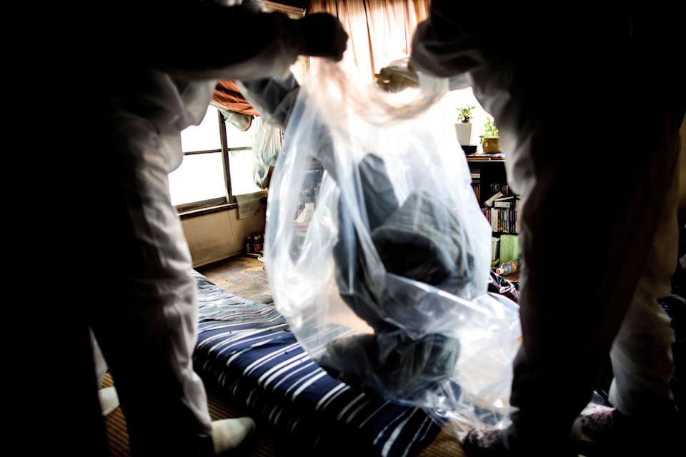 """In this picture taken on August 19, 2017, workers for special cleaning collect belongings of a man who died alone and left decomposing for three weeks, in his apartment in Tokyo. There are no official data for the number of people dying alone who stay unnoticed for days and weeks but most experts estimate it at 30,000 per year in Japan. The man, believed to be in his 50s, died alone in a city he shared with 13 million people but no one noticed, making him the latest victim of """"kodokushi"""" or """"dying alone"""" -- a growing trend in ageing Japan. / AFP PHOTO / BEHROUZ MEHRI / TO GO WITH AFP STORY JAPAN-DEATH-SOCIAL,FEATURE BY HIROSHI HIYAMA        (Photo credit should read BEHROUZ MEHRI/AFP/Getty Images)"""