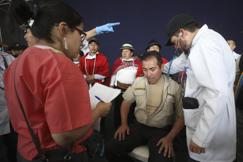 Doctors check the vitals of Col. Cristian Rueda Ramos, one of several police officers who has been detained by anti-government protesters, on a stage at the Casa de Cultura in Quito, Ecuador, Thursday, Oct. 10, 2019. An indigenous leader and four other people have died in unrest in Ecuador since last week, the public defender's office said Thursday. (AP Photo/Fernando Vergara)