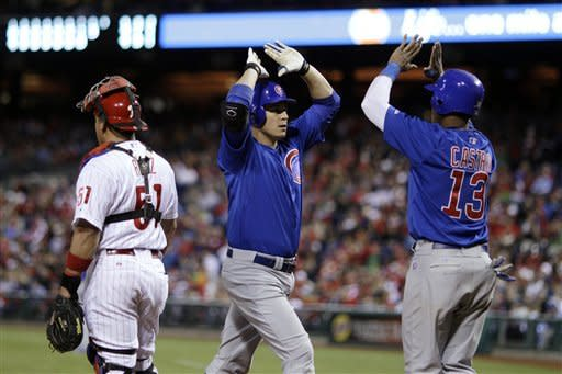 Chicago Cubs' Bryan LaHair, center, and Starlin Castro, right, celebrate after LaHair's two-run home run in the eighth inning of a baseball game against the Philadelphia Phillies, Monday, April 30, 2012, in Philadelphia. At left is Phillies catcher Carlos Ruiz. Philadelphia won 6-4. (AP Photo/Matt Slocum)
