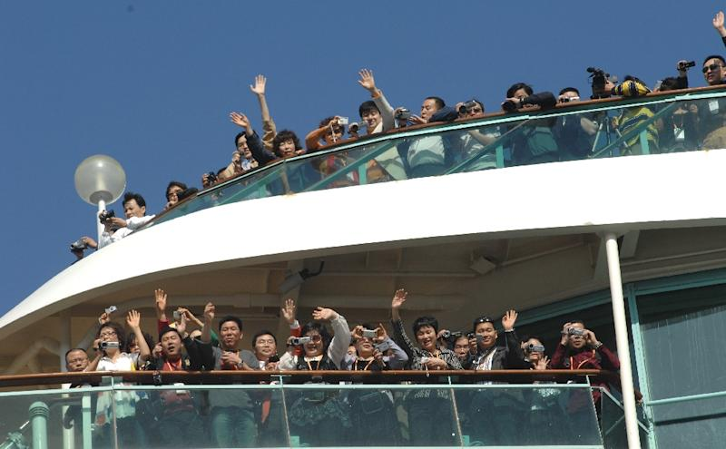 Mainland Chinese tourists wave upon their arrival at Taiwan's northern Keelung harbour