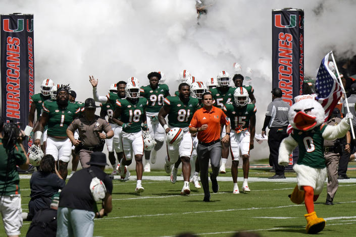 Miami head coach Manny Diaz runs onto the field with his players before an NCAA college football game against Central Connecticut State, Saturday, Sept. 25, 2021, in Miami Gardens, Fla. (AP Photo/Lynne Sladky)