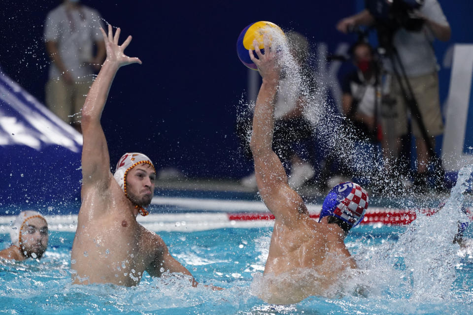 Croatia's Maro Jokovic (5) passes the ball over Spain's Alejandro Bustos Sanchez (12) during a preliminary round men's water polo match at the 2020 Summer Olympics, Monday, Aug. 2, 2021, in Tokyo, Japan. (AP Photo/Mark Humphrey)