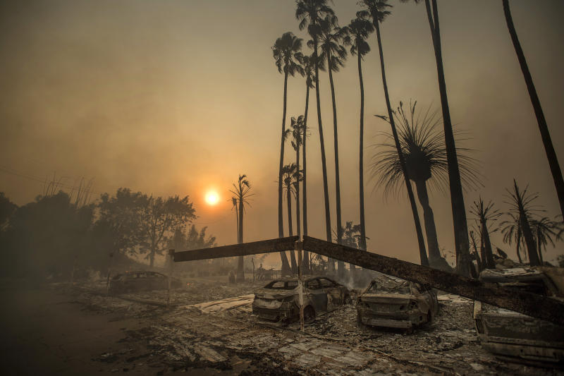 In this Dec. 5, 2017 file photo, smoke rises behind a destroyed apartment complex as a the Thomas wildfire burns in Ventura, Calif. (ASSOCIATED PRESS)