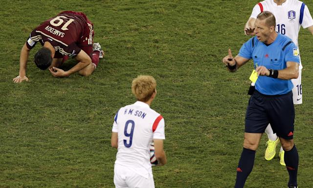 Referee Nestor Pitana, from Argentina, right, books South Korea's Son Heung-min (9) after he fouled Russia's Alexander Samedov (19) during the group H World Cup soccer match between Russia and South Korea at the Arena Pantanal in Cuiaba, Brazil, Tuesday, June 17, 2014. (AP Photo/Thanassis Stavrakis)