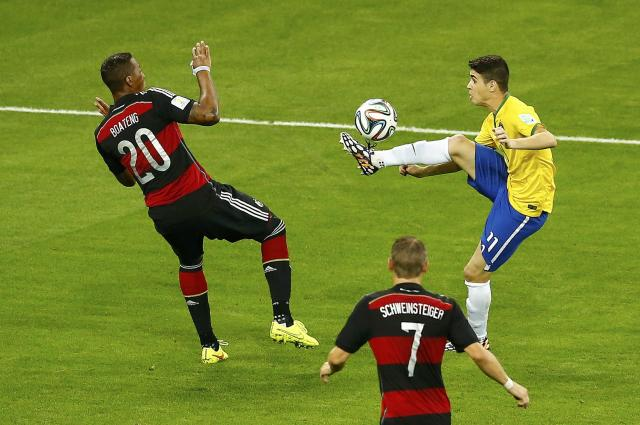 Brazil's Oscar (R) is challenged by Germany's Jerome Boateng (L) and Bastian Schweinsteiger during their 2014 World Cup semi-finals at the Mineirao stadium in Belo Horizonte July 8, 2014. REUTERS/Leonhard Foeger (BRAZIL - Tags: SOCCER SPORT WORLD CUP)