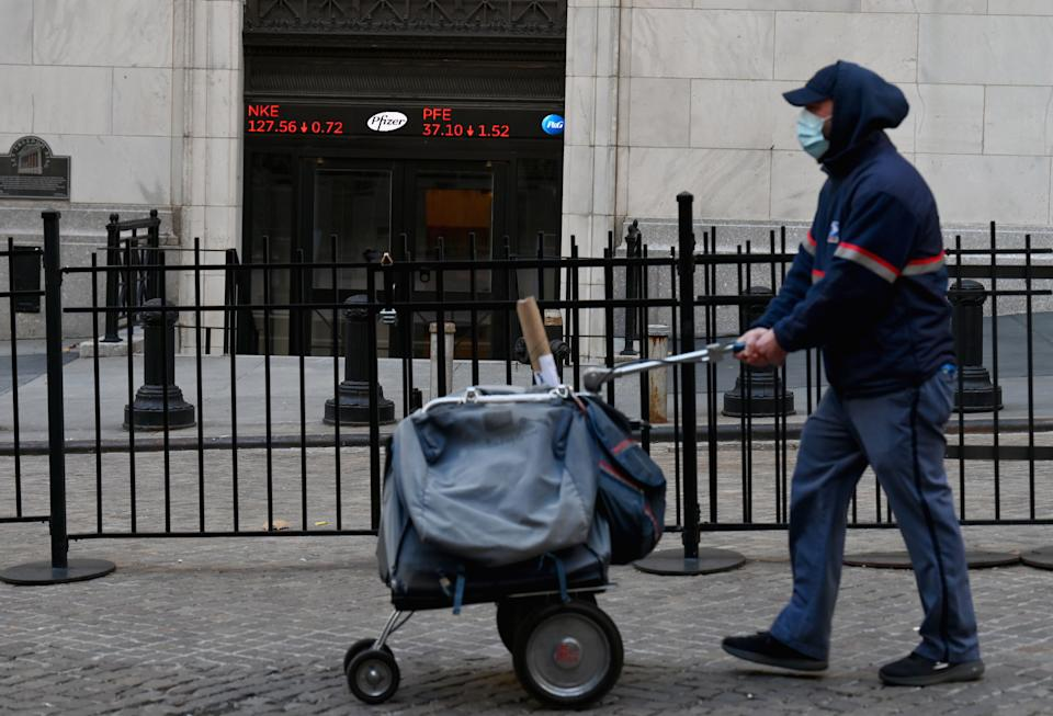 A USPS mail carrier walks past the New York Stock Exchange (NYSE) at Wall Street on November 16, 2020 in New York City. - Wall Street stocks rose early following upbeat news on a coronavirus vaccine and merger announcements in the banking and retail industries. (Photo by Angela Weiss / AFP) (Photo by ANGELA WEISS/AFP via Getty Images)