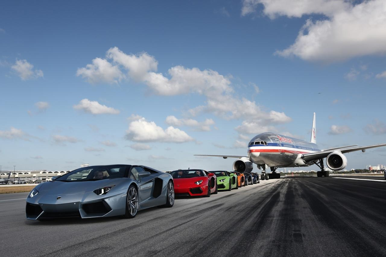 Lamborghini Aventador Roadsters race on the tarmac at Miami airport.