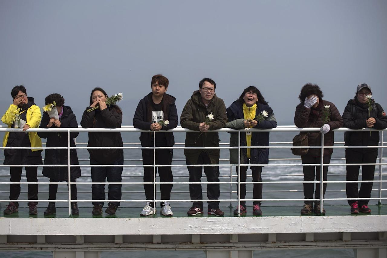 Relatives of victims of the Sewol ferry disaster weep as they stand on the deck of a boat during a visit to the site of the sunken ferry off the coast of South Korea's southern island of Jindo Wednesday, April 15, 2015.  A year ago, as South Korea writhed in grief and fury after more than 300 people, most of them school kids, drowned in a ferry sinking, it seemed things would never be the same. Yet not much has really changed as the first anniversary of the Sewol disaster is marked Thursday. (Ed Jones/Pool Photo via AP)