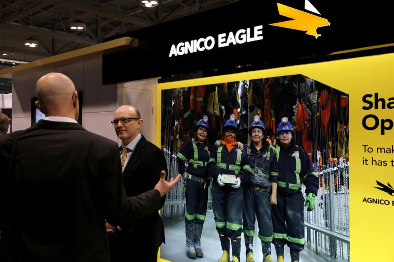 FILE PHOTO: A visitor speaks with a representative of Agnico Eagle Mines Ltd at the PDAC annual conference in Toronto