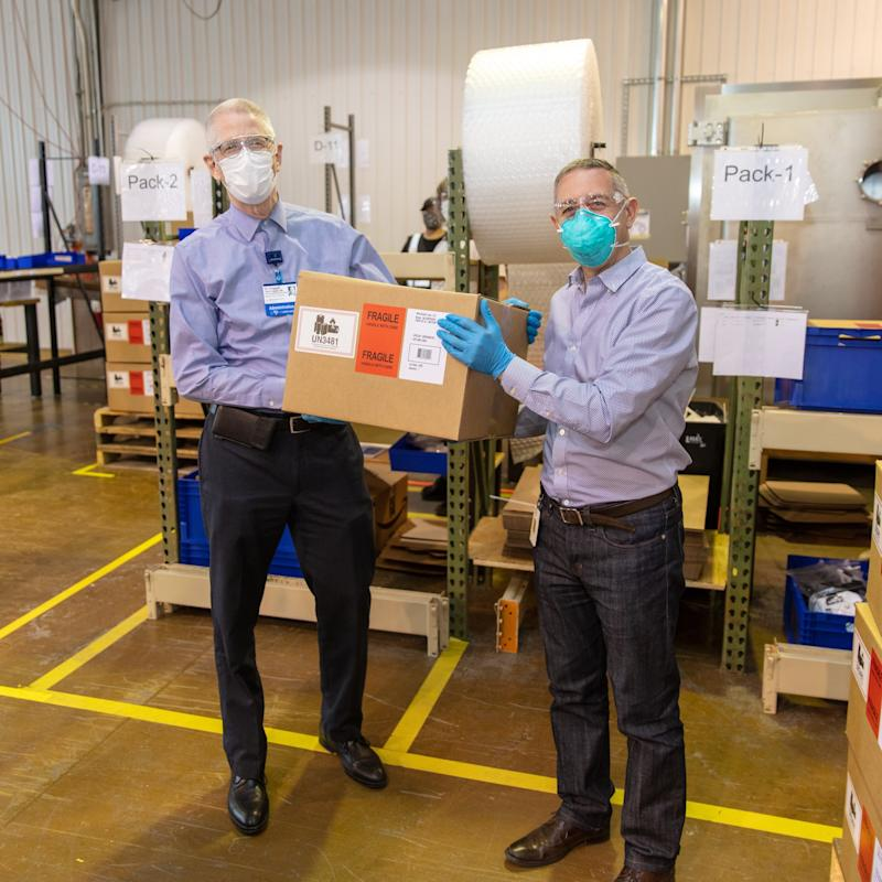 Dr. John Froggatt III receives the first box of PAPR units donated by Whirlpool Corporation, Dow, and Reynolds Consumer Products from Christian Gianni, President of WIN Health Labs and VP of Technology for Whirlpool Corporation. (Courtesy: Whirlpool)