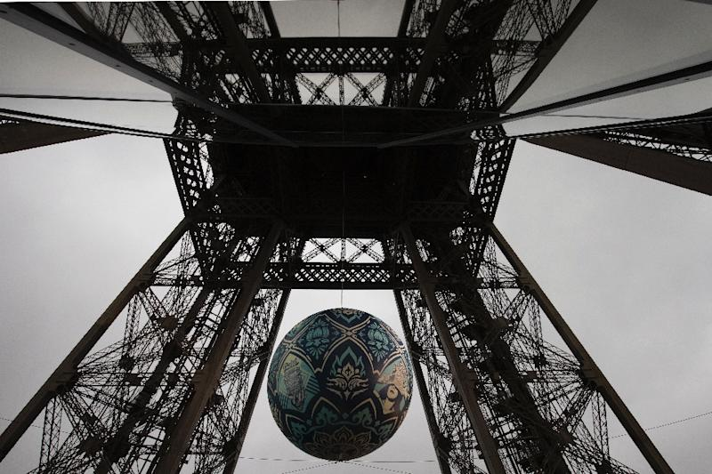 """A picture taken on November 20, 2015 shows the """"Earth Crisis"""" globe displayed by US artist Shepard Fairey on the Eiffel tower in Paris, as part of the organisation of the Conference on Climate Change COP21-CMP11 (AFP Photo/Joel Saget)"""