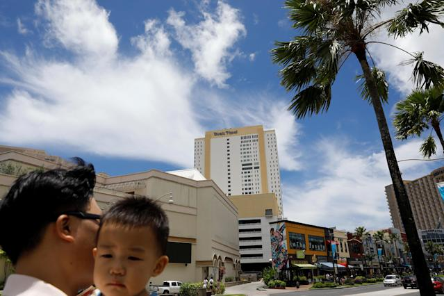 <p>A South Korean tourist carries his child in the Tumon tourist district on the island of Guam, a U.S. Pacific Territory, August 10, 2017. (Erik De Castro/Reuters) </p>