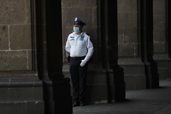 """A police officer wearing protective gear against the spread of the new coronavirus, stands guard outside the mayor's office, in the historic center of Mexico City, Wednesday, April 1, 2020, where many businesses have temporarily closed. Mexico's government has broadened its shutdown of """"non essential activities,"""" and prohibited gatherings of more than 50 people as a way to help slow down the spread of COVID-19. (AP Photo/Marco Ugarte)"""