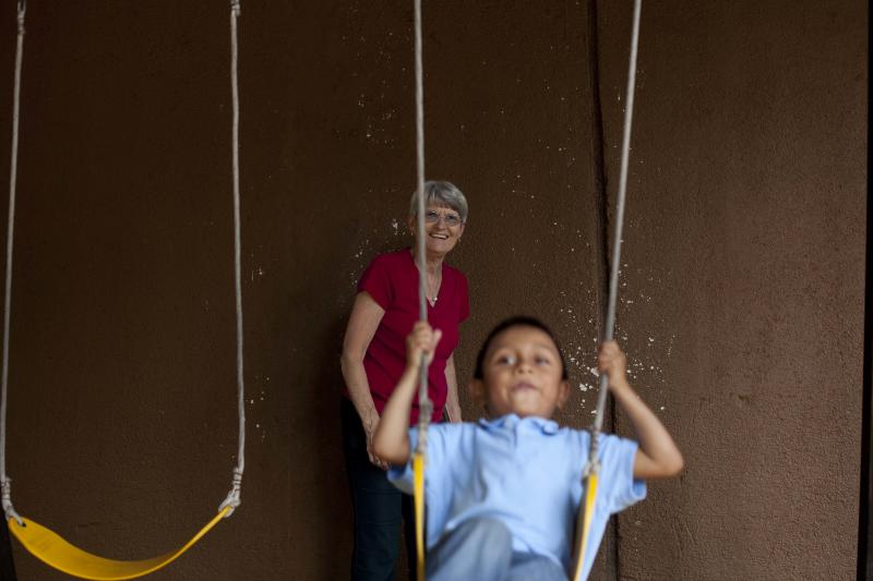 In this Friday, Sept. 7, 2012 photo, Judy Russell, left, watches her adopted grandson Daniel swing at at a restaurant in Guatemala City. Daniel was 18 months old when Russell's daughter, Jessica Hooker and her husband Ryan began the process to adopt him in Guatemala. They just got him at age 6. His is one of hundreds of adoption cases that were put in limbo five years ago, when the Guatemalan government declared a moratorium on international adoptions because of irregularities and fraud. (AP Photo/Moises Castillo)