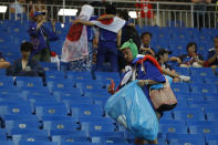 <p>A fan of Japan collects trash after the round of 16 match between Belgium and Japan at the 2018 soccer World Cup in the Rostov Arena, in Rostov-on-Don, Russia, Monday, July 2, 2018. Japan lost 2-3. (AP Photo/Pavel Golovkin) </p>