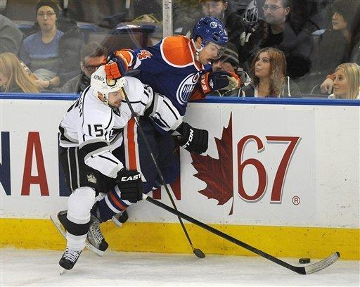 Los Angeles Kings' Brad Richardson, left, checks the Edmonton Oilers' Taylor Hall during the third period of an NHL hockey game in Edmonton, Alberta, on Sunday, Jan. 15, 2012. (AP Photo/The Canadian Press, John Ulan)