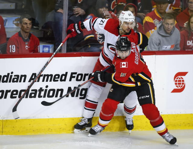 Carolina Hurricanes' Nino Niederreiter, left, of Switzerland, is checked by Calgary Flames' Mark Giordano during first period NHL hockey action in Calgary, Tuesday, Jan. 22, 2019. (Jeff McIntosh/The Canadian Press via AP)