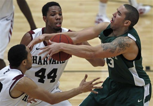 Dartmouth forward Jvonte Brooks, right, loses control of the ball as he is pressured by Harvard forward Andrew Van Nest, left, and forward Keith Wright (44) in the second half of an NCAA college basketball game in Cambridge, Mass., Saturday Jan. 7, 2012. (AP Photo/Charles Krupa)
