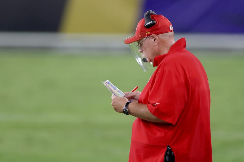 Andy Reid looks down at his playcard while wearing a face shield.