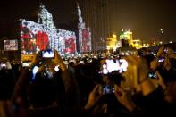 Visitors take pictures and videos during a light show as part of a New Year countdown celebration as part of a New Year countdown celebration on the Bund in Shanghai January 1, 2014. REUTERS/Aly Song