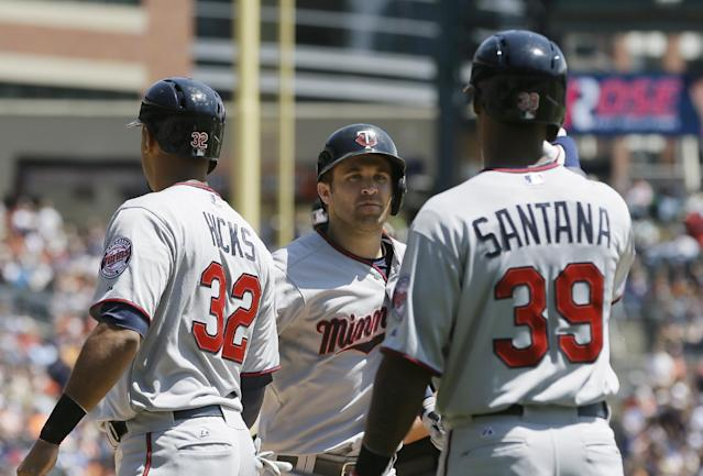 Minnesota Twins' Brian Dozier, center, is greeted by teammates Aaron Hicks (32) and Danny Santana (39) after they scored on Dozier's three-run home run during the third inning of a baseball game against the Detroit Tigers in Detroit, Saturday, May 10, 2014. (AP Photo/Carlos Osorio)