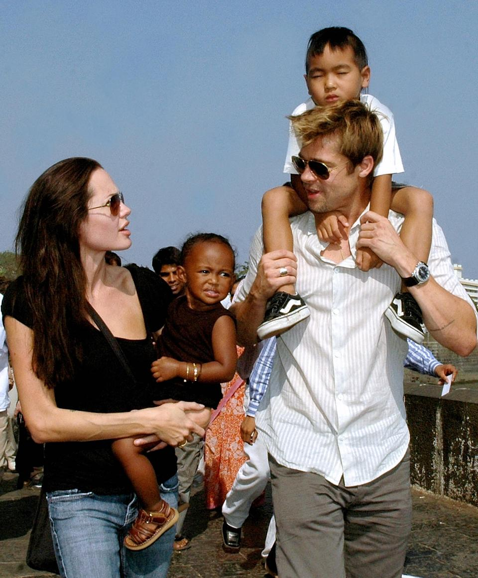"""Angelina Jolie (L), daughter Zahara (2L), then-husband Brad Pitt (R), and son Maddox take a stroll on the seafront promenade in Mumbai, 12 November 2006.  Jolie and Pitt are in Mumbai, India's financial hub, to shoot for her film """"A Mighty Heart"""", based on the life of the slain Wall Street Journal reporter Daniel Pearl in which Jolie portrays Marianne, the wife of Daniel Pearl.  AFP PHOTO/STR  (Photo credit should read STR/AFP via Getty Images)"""