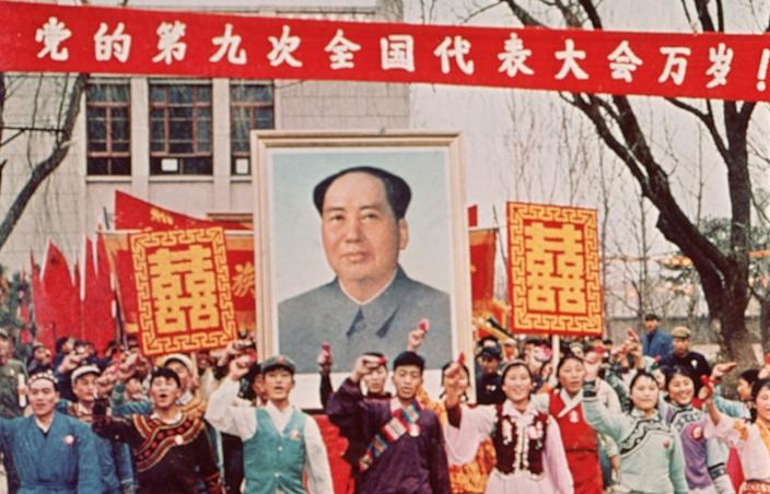 """People march carrying a large poster of Chairman Mao Zedong during the Cultural Revolution in China in 1968. <span class=""""copyright"""">(Hulton Archive )</span>"""