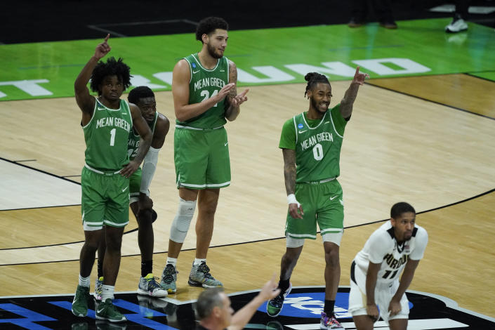 North Texas's Mardrez McBride, Thomas Bell (13), Zachary Simmons (24) and James Reese (0) react as Javion Hamlet shoots free throws during overtime of a first-round game against Purdue in the NCAA men's college basketball tournament at Lucas Oil Stadium, Friday, March 19, 2021, in Indianapolis. North Texas defeated Purdue 78-69 in overtime. (AP Photo/Darron Cummings)
