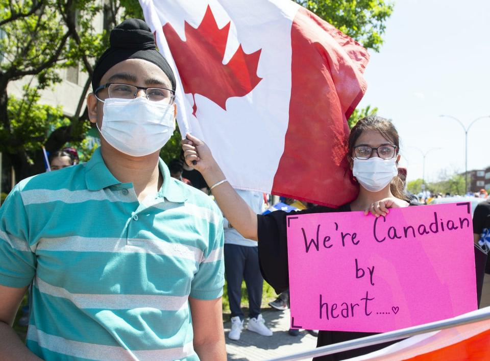 People wearing masks hold signs at a rally