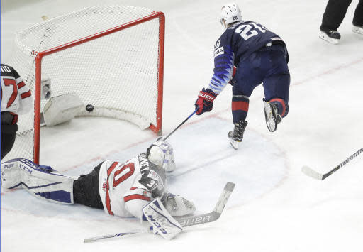 Chris Kreider of the United States, right, scores his side's first goal to Canada's goalie Curtis McElhinney during the Ice Hockey World Championships bronze medal match between Canada and the United States at the Royal arena in Copenhagen, Denmark, Sunday, May 20, 2018. (AP Photo/Petr David Josek)