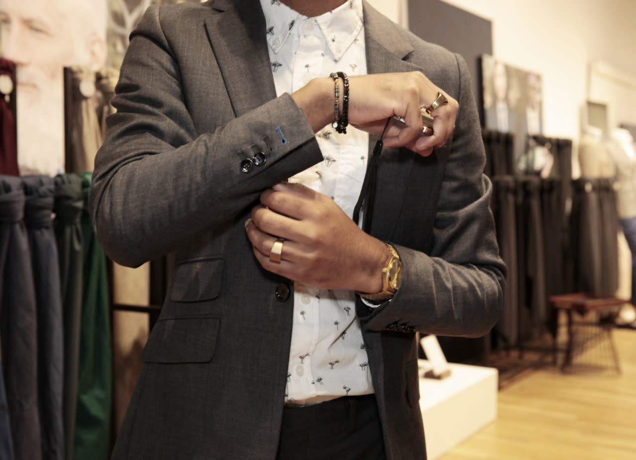 """<p>Aaron Brocket, Quinn's handy helper and distinguished showroom team lead at Indochino's popular SoHo store, demonstrates the level of personalization with his blue stitched details (and the stylish extra pocket flap). Brocket also provided Quinn with some helpful styling tips — for example, """"for a wider-chested man, you should opt for a wider-lapel jacket.""""(Photo: Alexis Brooks for Yahoo Style)</p>"""