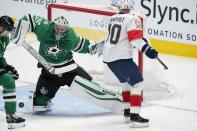 Dallas Stars goaltender Anton Khudobin (35) deflects a shot as Florida Panthers right wing Patric Hornqvist (70) skates past in the second period of an NHL hockey game in Dallas, Saturday, April 10, 2021. (AP Photo/Tony Gutierrez)