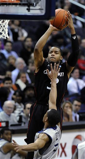 Cincinnati's Dion Dixon goes up for a 3-pointer against the defense of Georgetown's Markel Starks during first half of an NCAA college basketball game Monday, Jan. 9, 2012, in Washington. Cincinnati defeated Georgetown 68-64. (AP Photo/Richard Lipski)
