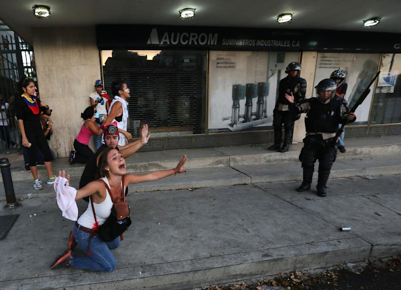 An opposition demonstrator shouts for the National Bolivarian Police (BNP) to not fire tear gas as a member of the force, right, gestures after his superior ordered them to hold their fire, during clashes in Caracas, Venezuela, Saturday, Feb. 15, 2014. Venezuelan security forces backed by water tanks, tear gas and rubber bullets dispersed groups of anti-government demonstrators who tried to block Caracas' main highway Saturday evening. (AP Photo/Fernando Llano)