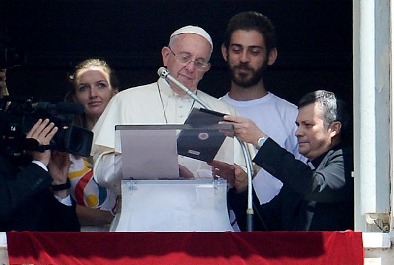 Pope Francis, accompanied by two Polish youths, uses an iPad to register online for the next 2016 World Youth Day in Poland during the Angelus prayer at the Vatican on July 26, 2015