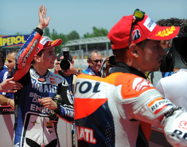 Repsol Honda Team's Australian Casey Stoner (R) and Yamaha Factory Racing's Spanish Jorge Lorenzo celebrate at the Catalunya racetrack in Montmelo, near Barcelona, on June 2, 2012, after the MotoGP qualifying session of the Catalunya Moto GP Grand Prix. AFP PHOTO/LLUIS GENELLUIS GENE/AFP/GettyImages