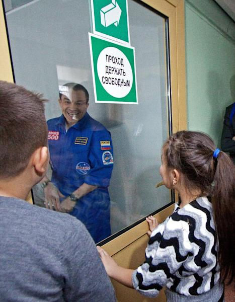 FILE - This Nov. 4, 2011 file photo released by Moscow's Institute for Medical and Biological Problems Russian shows researcher Sukhrob Kamolov greeting his relatives after completing a grueling 520-day simulation of a flight to Mars. Astronauts have a down-to-Earth problem that could be even worse on a long trip to Mars: They can't get enough sleep. And over time, the lack of slumber can turn intrepid space travelers into drowsy couch potatoes, a new study shows. In a novel experiment, six volunteers were confined in a cramped mock spaceship in Moscow to simulate a 17-month voyage. It made most of the would-be spacemen act like birds and bears heading into winter, gearing for hibernation. (AP Photo/IMBP, Oleg Voloshin, Pool, File)