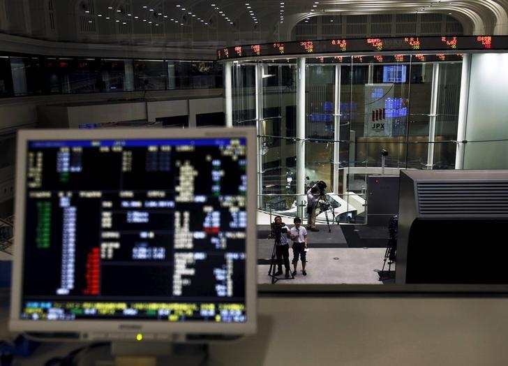 A videographer films an electronic board showing the Japan's Nikkei average at the Tokyo Stock Exchange (TSE) in Tokyo, Japan, July 9, 2015. REUTERS/Yuya Shino/Files
