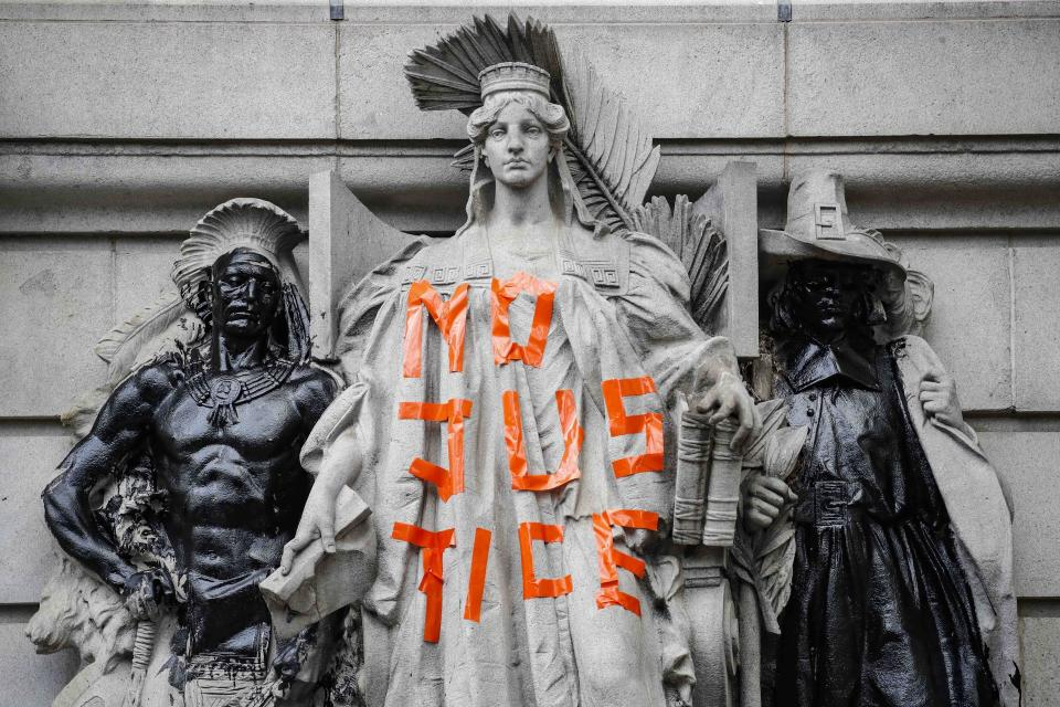Statues are defaced outside government buildings as protesters gather at an encampment outside City Hall, Tuesday, June 30, 2020, in New York. New York City lawmakers are holding a high-stakes debate on the city budget as activists demand a $1 billion shift from policing to social services and the city grapples with multibillion-dollar losses because of the coronavirus pandemic. (AP Photo/John Minchillo)