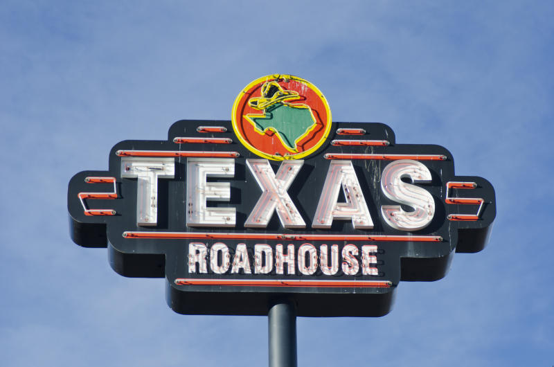 Colorado Springs, United States - November 17, 2011: A Texas Roadhouse restaurant is easy to locate because of this neon sign, photographed against a blue sky, with plenty of copy space available.