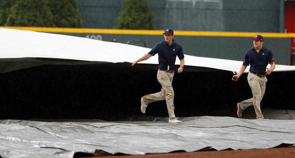 Members of the Atlanta Braves grounds crew rush to cover the infield during a rain shower during the fifth inning of the first game of a baseball doubleheader against the New York Mets. Monday, May 28, 2018, in Atlanta. (AP Photo/John Bazemore)