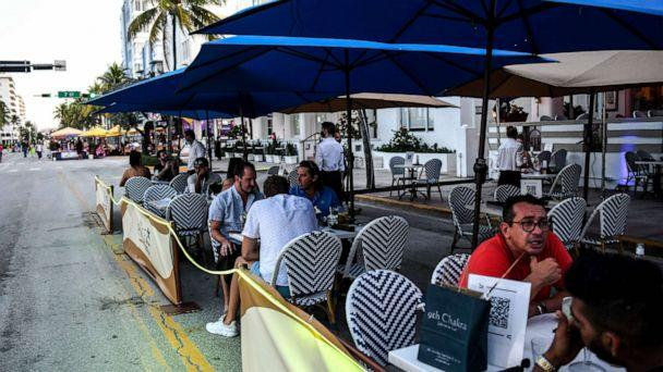 PHOTO: People eat in the outdoor dining area of a restaurant on Ocean Drive in Miami Beach, Florida on June 24, 2020. (Chandan Khanna/AFP via Getty Images)