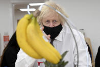 British Prime Minister Boris Johnson looks at a bunch of bananas to draw during a visit to the Monkey Puzzle Nursery in Greenford, west London, Thursday, March 25, 2021. (Jeremy Selwyn/Pool Photo via AP)