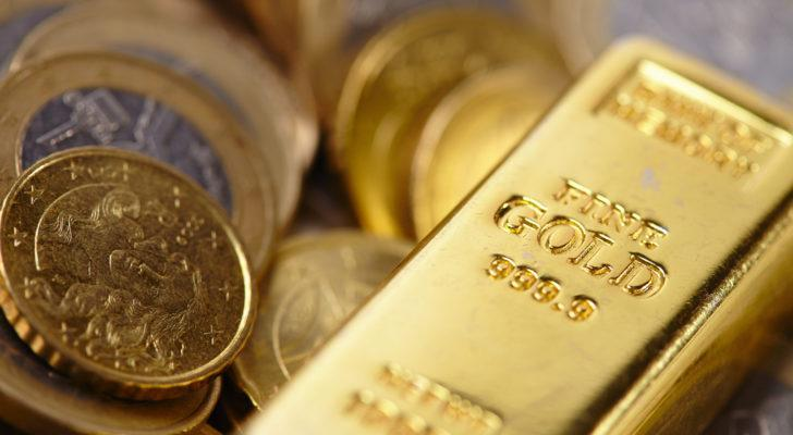 A gold bar along with some coins made of precious metals. gold stocks